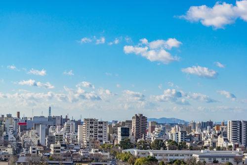 青空の下にビルや家が建ち並んでいる風景