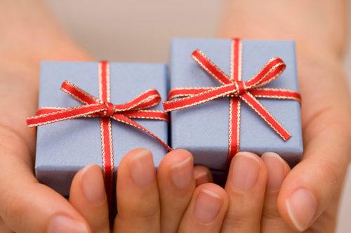 小さな2つのプレゼントを手のひらで持っている手元